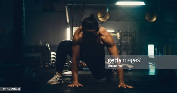 ダークジムでの女性ファイターワークアウト。プッシュアップ - 自重トレーニング ストックフォトと画像