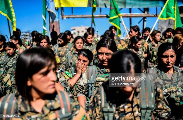 Female fighters of the Syrian Democratic Forces gather during a celebration at the iconic AlNaim square in Raqa on October 19 after retaking the city...