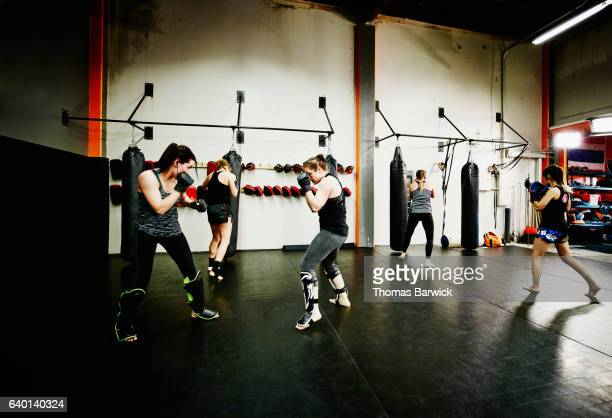 female fighters working out together in fighting gym - 総合格闘技 ストックフォトと画像