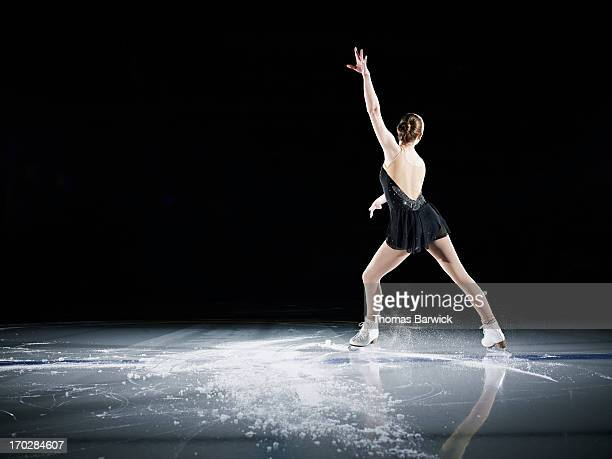 female figure skater performing on ice rink - patinage artistique photos et images de collection