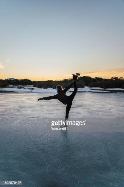 female figure skater practicing on frozen lake at dusk - eiskunstlauf stock-fotos und bilder