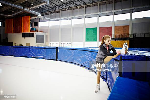 female figure skater stretching on ice rink wall - figure skating stock pictures, royalty-free photos & images