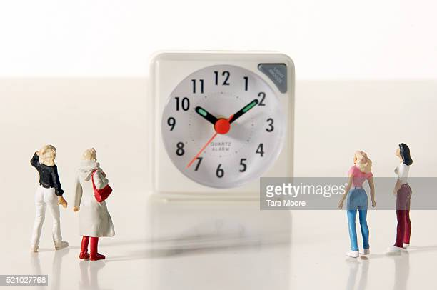 Female Figurines Looking at Clock