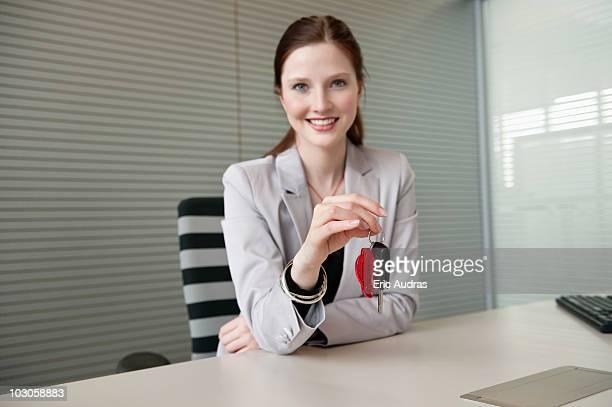 Female financial advisor holding a car key in an office