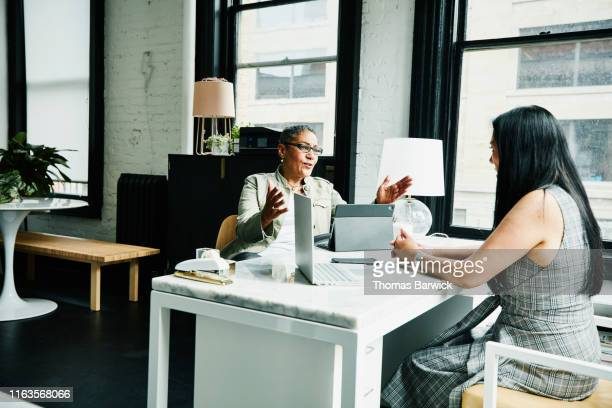 female financial advisor in discussion with mature female business owner at desk in office - financial occupation stock pictures, royalty-free photos & images