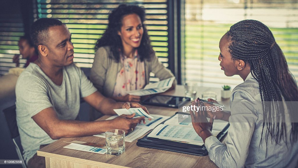 Female financial advisor talking to a couple at home : Stock Photo