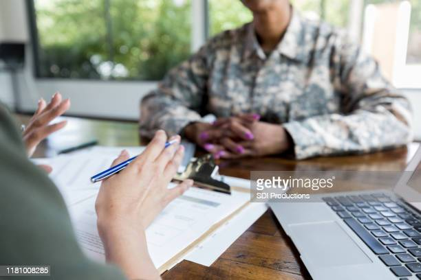 female financial advisor talks with veteran - veteran stock pictures, royalty-free photos & images