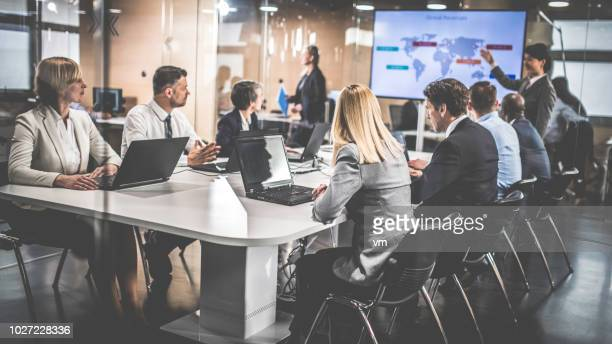 female financial analyst giving presentation to board members - globalization stock pictures, royalty-free photos & images