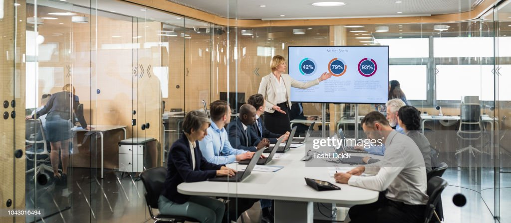 Female Financial Analyst Giving Presentation To Board Members : Stock Photo