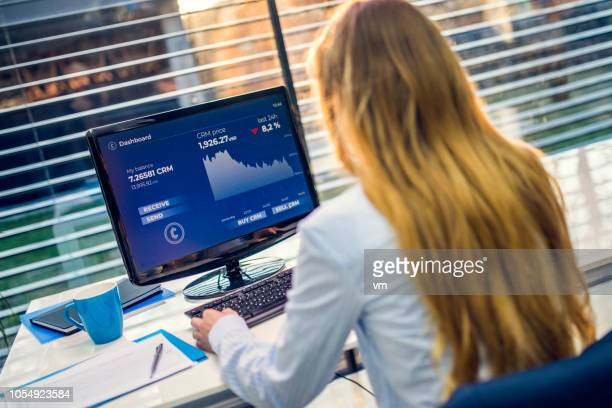 female financial analyst studying cryptocurrency graph on her office computer - financial analyst stock photos and pictures