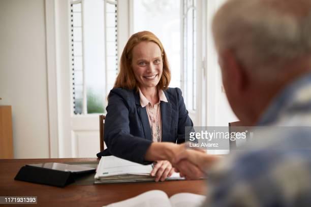 female financial consultant meeting with retired man at home - finanzen und wirtschaft stock-fotos und bilder