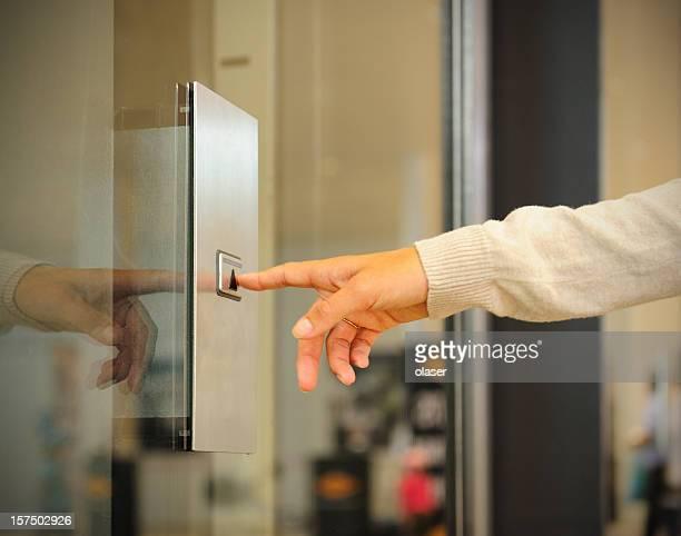 女性の指のエレベーターのボタンを押す