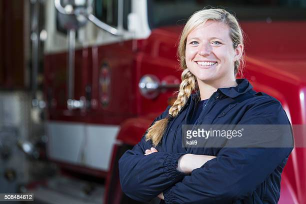 Female fire fighter standing by truck at the station