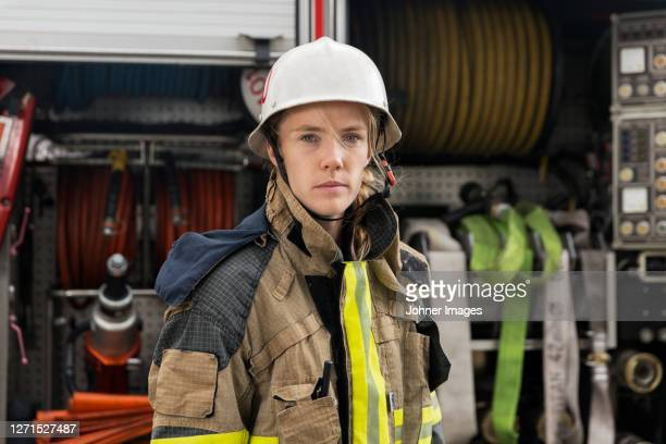 female firefighter by fire engine - firefighter stock pictures, royalty-free photos & images