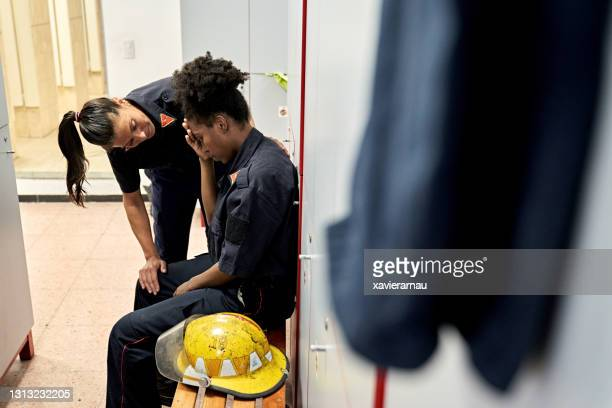 female firefighter giving emotional support to teammate - firefighter stock pictures, royalty-free photos & images