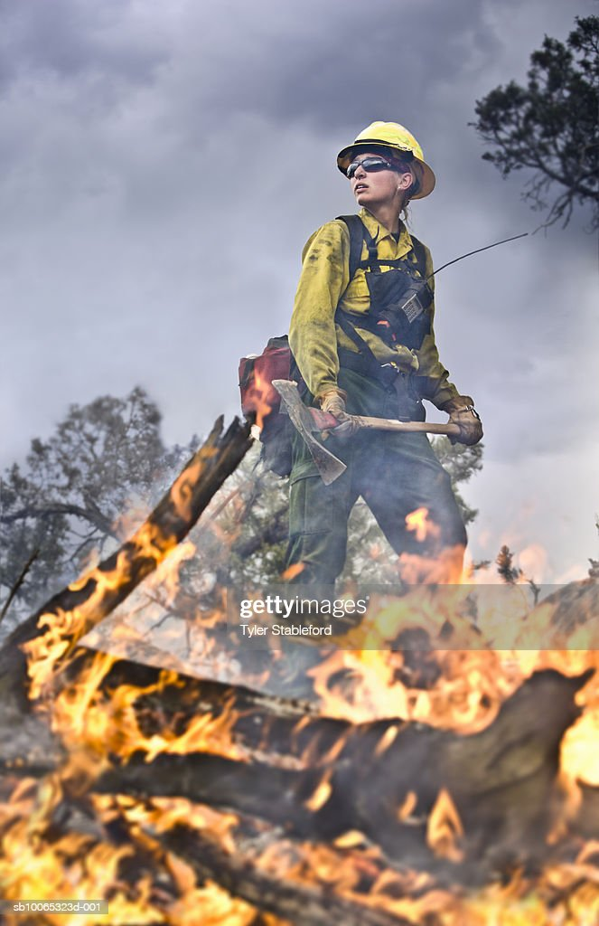 Female fire-fighter holding pickaxe near burning branch : Foto stock