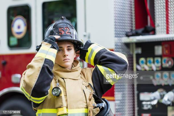 female firefighter in fire protection suit - firefighter stock pictures, royalty-free photos & images