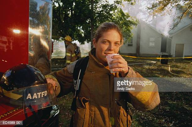 Female firefighter in front of burnt out building, drinking water