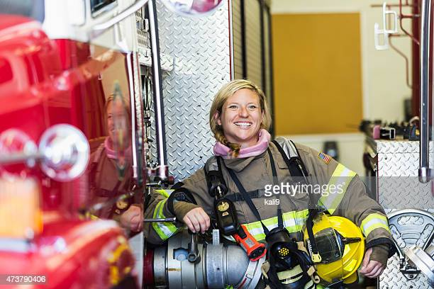 female firefighter standing beside fire truck at station - fire station stock photos and pictures