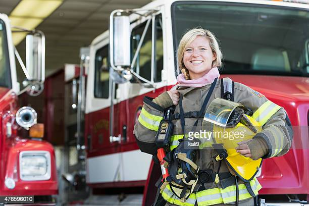 female firefighter standing in front of fire truck - firefighter stock pictures, royalty-free photos & images