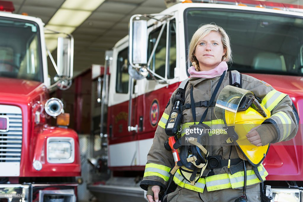 Female firefighter standing in front of fire truck : Stock Photo