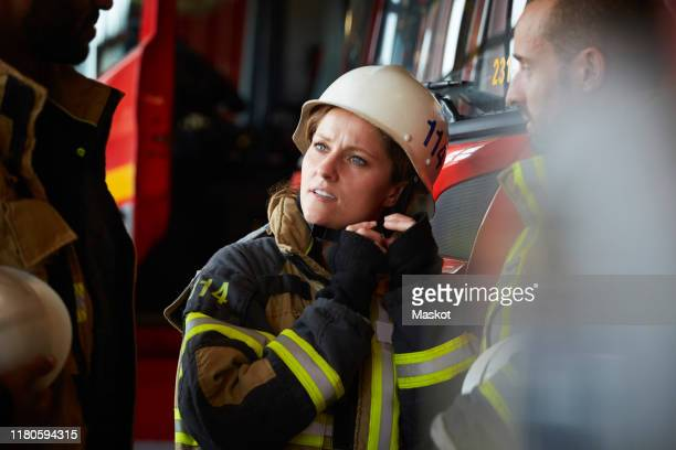 female firefighter wearing helmet while talking with other coworkers in fire station - firefighter stock pictures, royalty-free photos & images