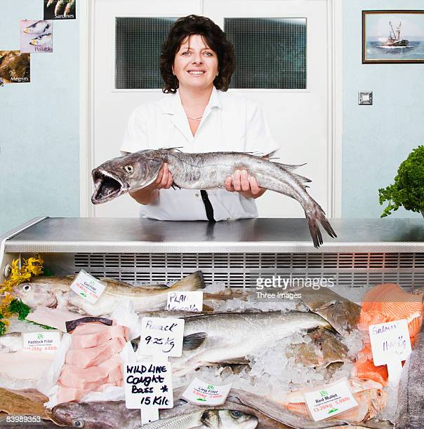 Female fish monger with selection of fish