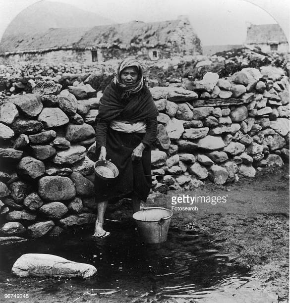 A female fisherman from Kerry Ireland standing before a drystone wall with buildings beyond 19th Century