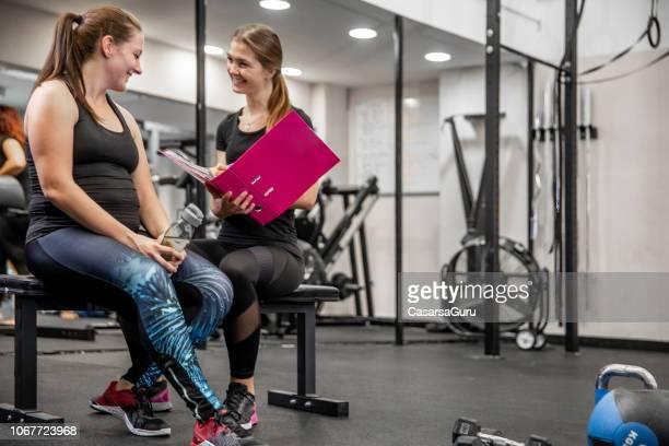 istruttore di fitness femminile che va attraverso il programma di allenamento scritto con il suo cliente - allenatore foto e immagini stock