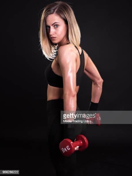 Instructeur de fitness femmes tenant des haltères rouges en face de fond noir
