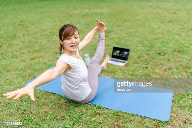 公共の公園でラップトップ上のビデオ通話を介してオンラインヨガやピラティスを教える女性フィットネスインストラクター - 体への関心 ストックフォトと画像