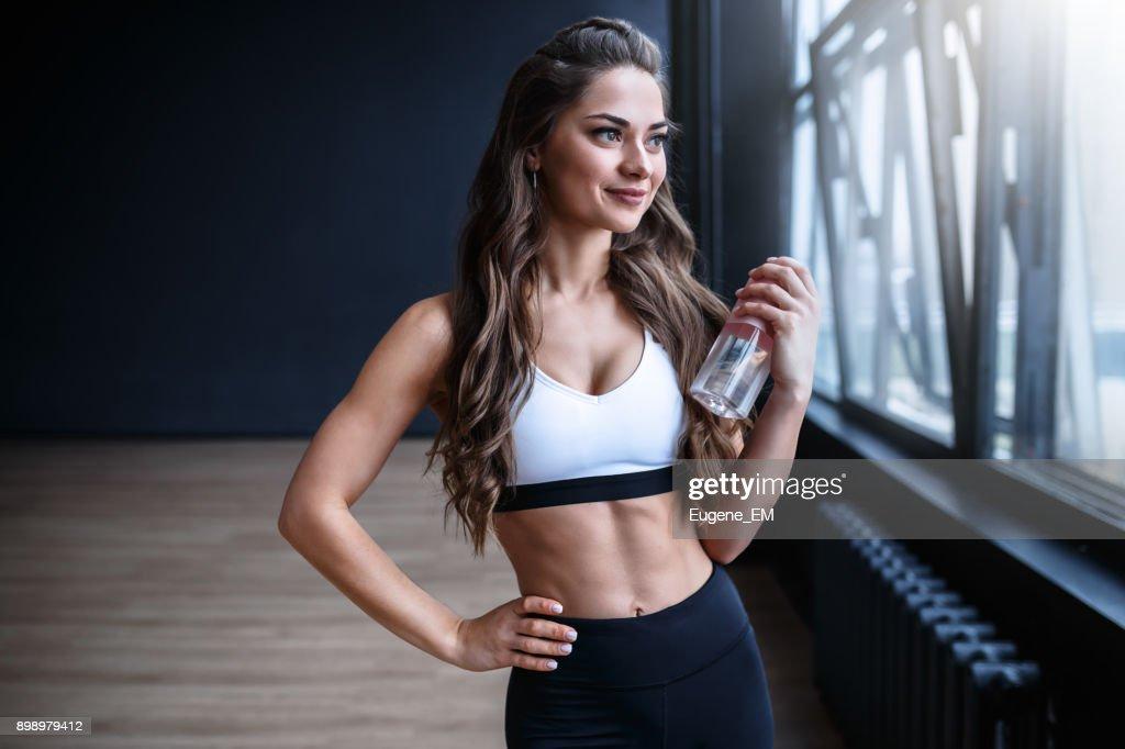 Female fitness model in white top and black leggings is posing near the big windows in studio in morning time : Stock Photo