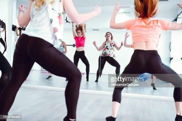 Female Fitness Team Dancing And Working Out With Zumba Exercises In Gym