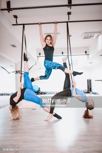 Female Fitness Team Doing Aerial Yoga Exercises In Gym Together