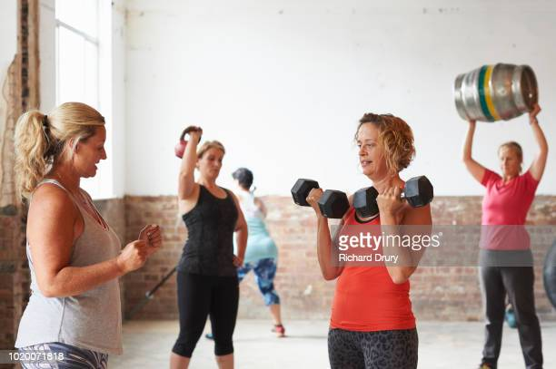 female fitness trainer instructing woman lifting dumbbells - richard drury stock pictures, royalty-free photos & images