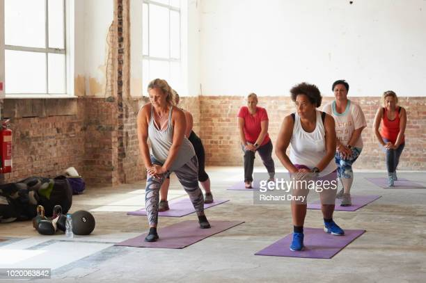 female fitness trainer leading a class at the gym - fitness or vitality or sport and women stock photos and pictures