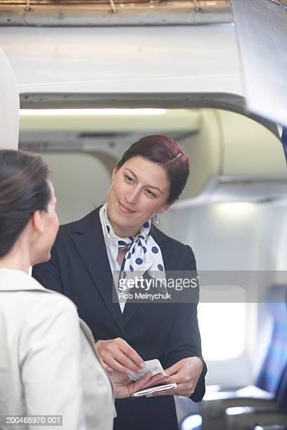 Female flight attendant checking passenger's boarding pass