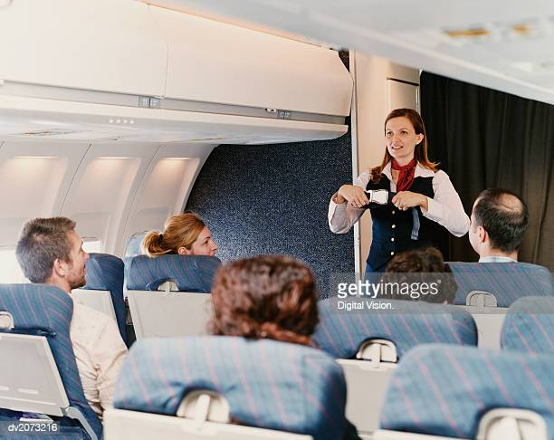female flight attendant demonstrating safety procedures to passengers on a plane - crew stock pictures, royalty-free photos & images