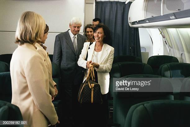 Female flight attendant standing in airplane welcoming passengers