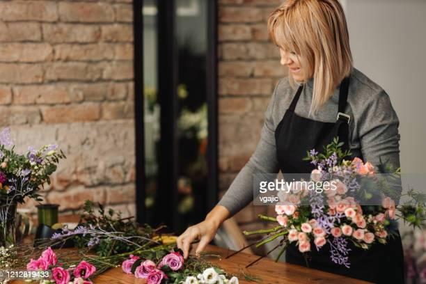 female florist arranging bouquet in flower shop - molho arranjo imagens e fotografias de stock