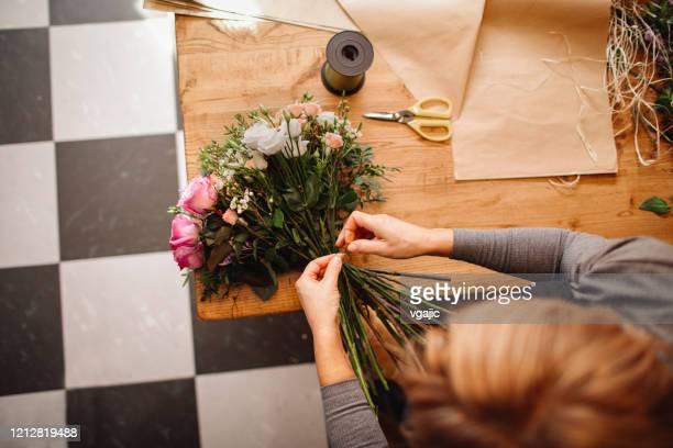female florist arranging bouquet in flower shop - arranging stock pictures, royalty-free photos & images
