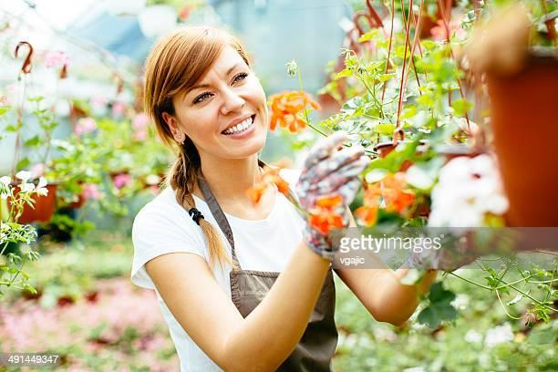 Fêmea Florista cuidado com Flores no jardim de viveiro.