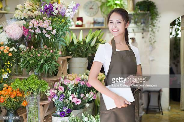Female florist holding digital tablet in shop