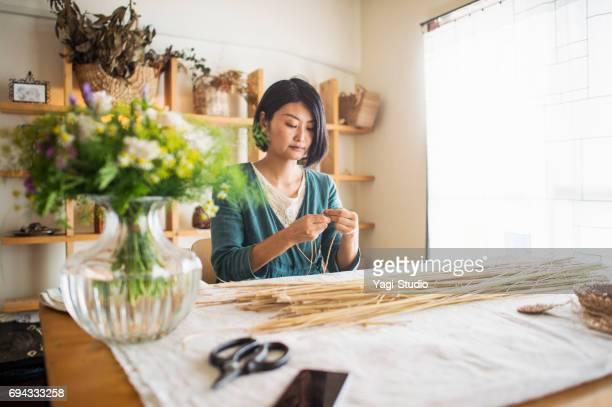 Fleuriste femelle faisant une paille tricot et produits de la marque en studio