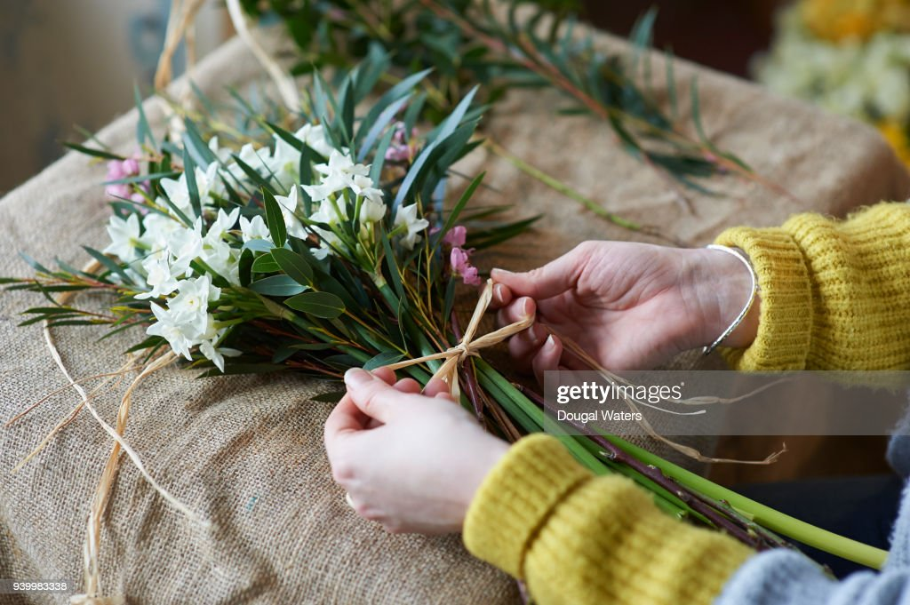 Female florist making bunch of flowers close up. : Stock Photo