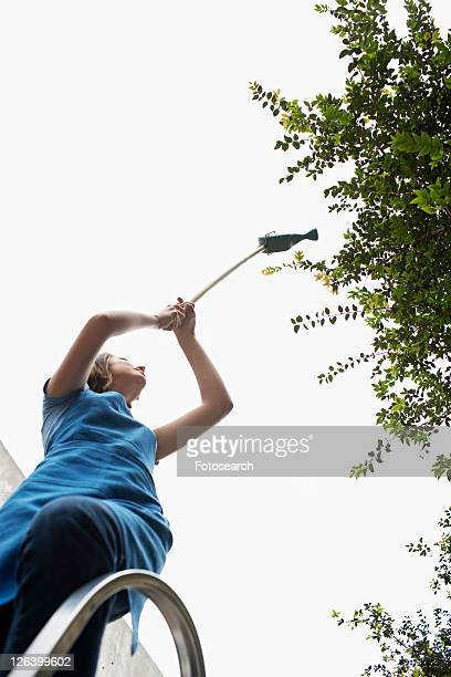 Female Florist on Step Ladder Watering Plants