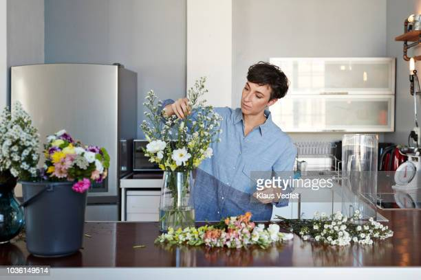 female florist organising flowers for customer from home - flower arrangement stock pictures, royalty-free photos & images