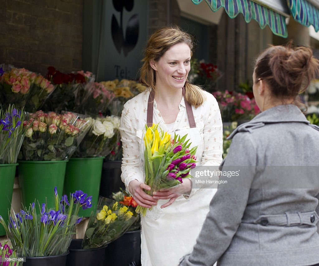 Female Florist Servicing Customer : Stock Photo