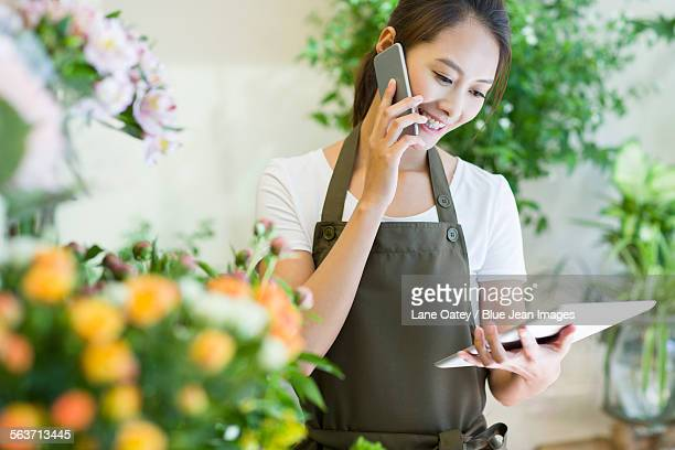 Female florist talking on the phone in shop