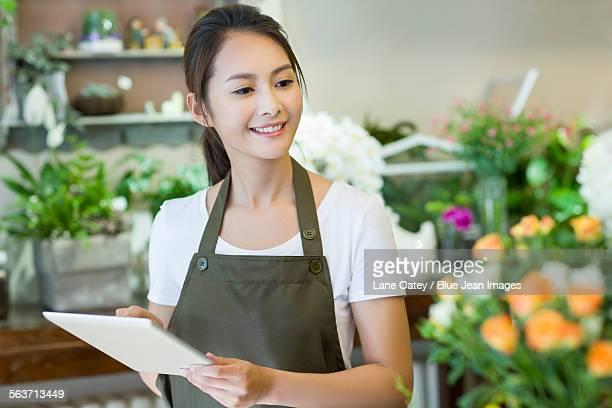 Female florist using digital tablet in shop
